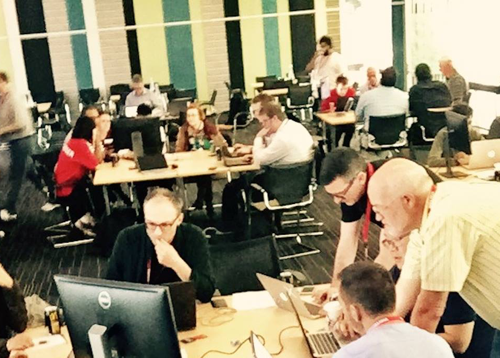 A picture of groups of people working at different tables during a hackathon